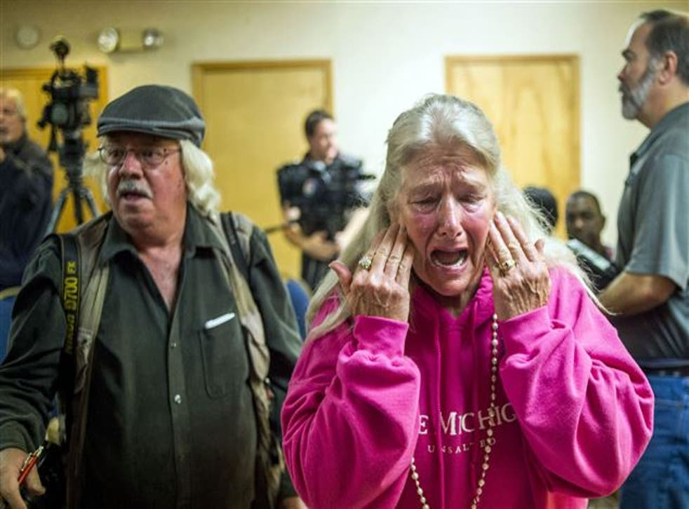 Flint resident Gladyes Williamson cries as lawsuit is filed