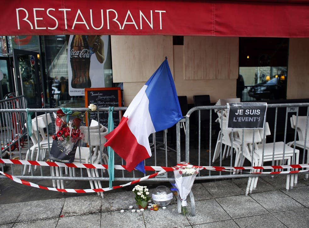 The French flag and floral tributes are displayed on a barrier near a restaurant hit by the terror attacks near the Stade De France stadium in Saint-Denis