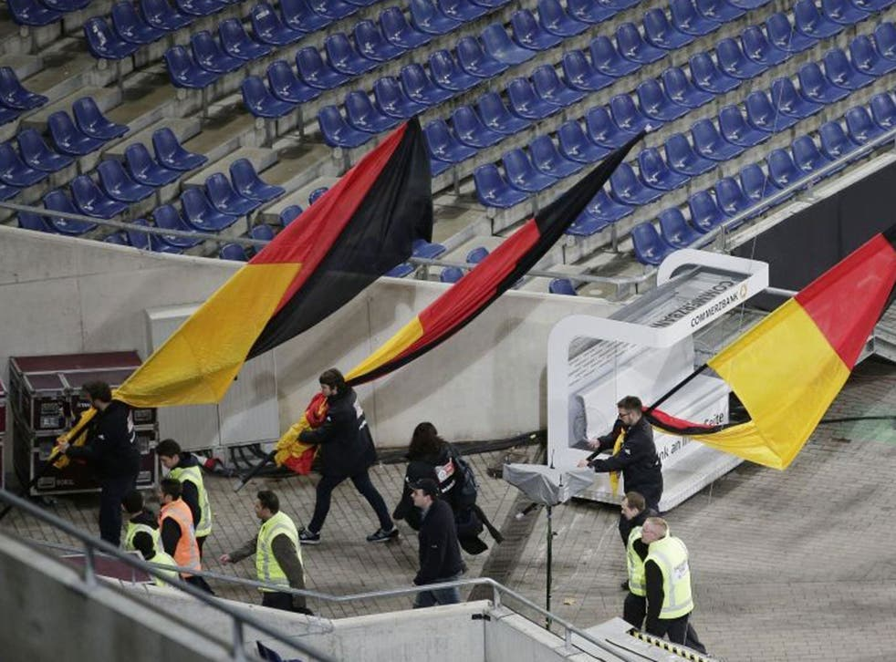 German flags are carried out of the Hannover stadium as the soccer friendly between Germany and the Netherlands was cancelled