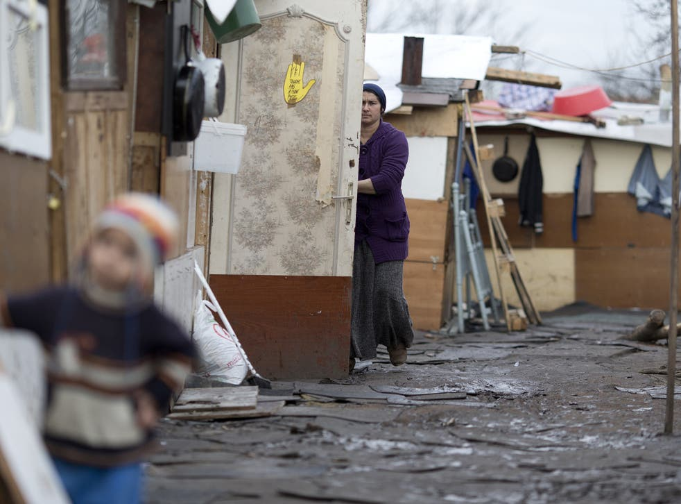 A woman from the Roma community works at the entrance of her shack in a camp in Stains, outside Paris