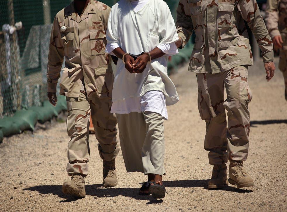 US Navy guards escort a detainee at Guantanamo Bay.