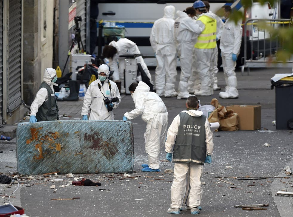 Forensic officers search for evidence following the raid on a building in Saint-Denis
