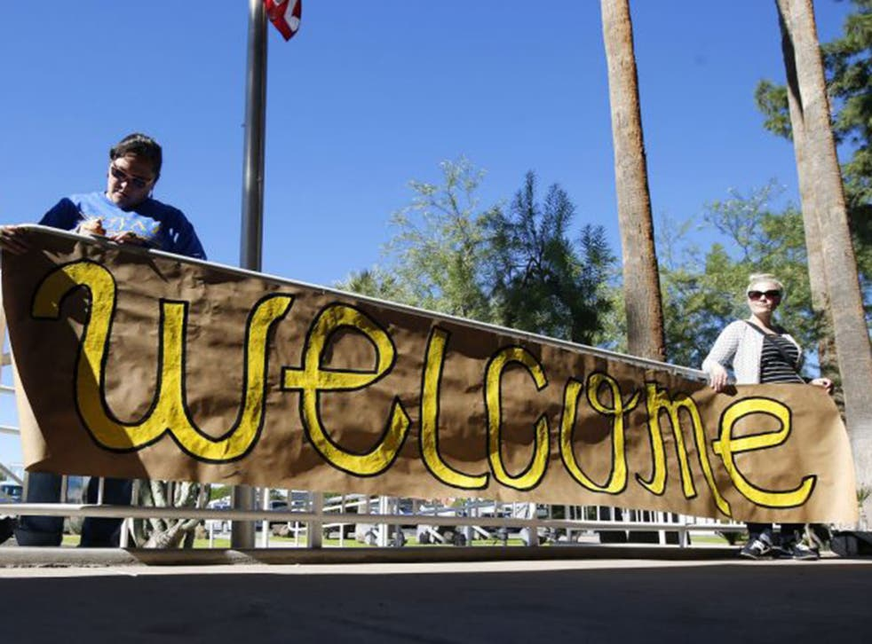 Supporters place a sign welcoming Syrian refugees is placed at the entrance to the office of Arizona's governor