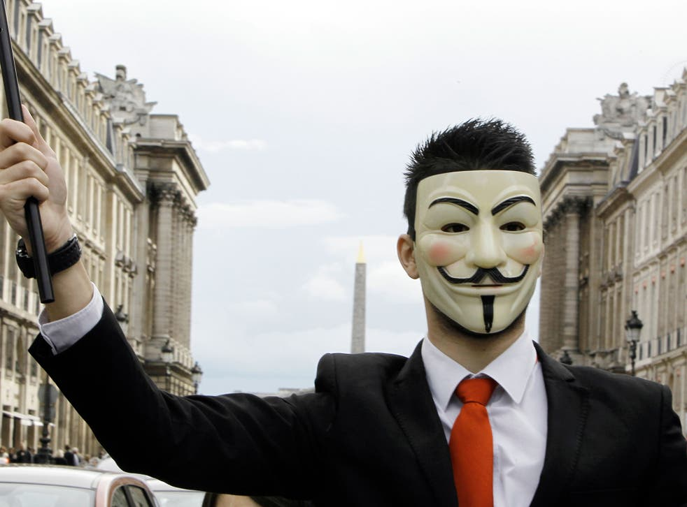 A protester wearing an Anonymous Guy Fawkes mask takes part in a demonstration in front of the Concorde square in Paris, as part of a 'popular march' gathering Anonymous and Indignant protesters, to denounce an 'electoral farce', on April 21, 2012, on the eve of the first-round poll of French presidential election