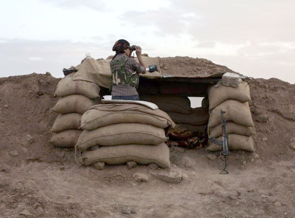 A Kurdish fighter surveys the border between Turkey and Iraq in early 2015