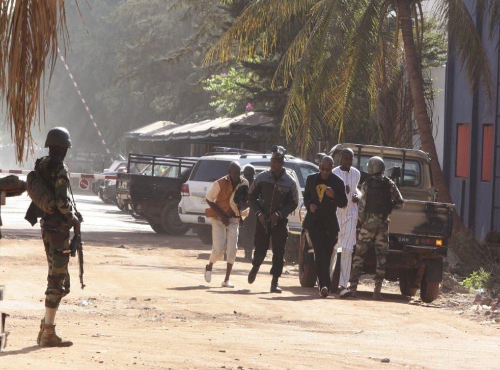People flee the Radisson Blu hotel after it was stormed by gunmen