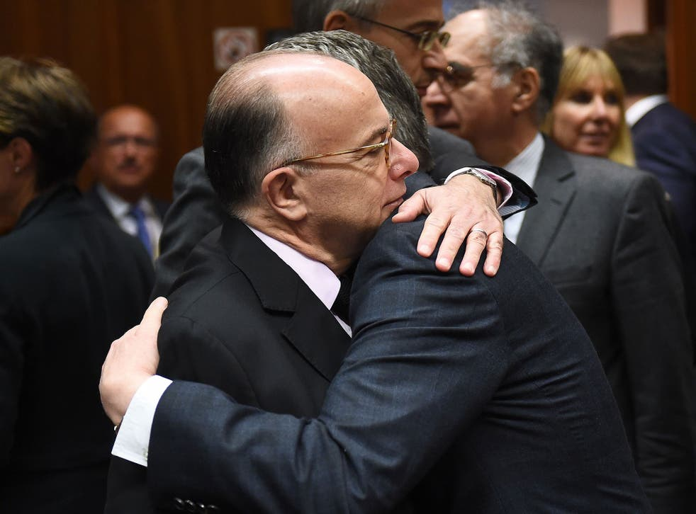 German Interior Minister Thomas de Maiziere (R) embraces French Interior Minister Bernard Cazeneuve during a meeting at the European Council in Brussels on 20 November