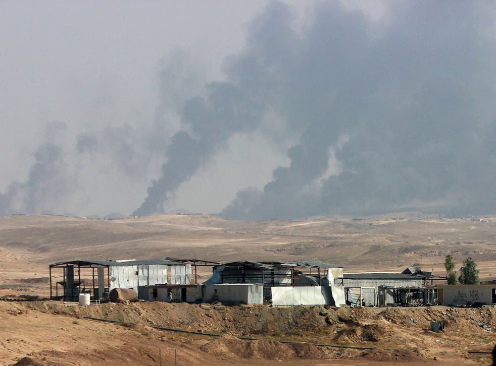 Smoke rises as Iraqi security forces and allied Popular Mobilization Forces shell Islamic State group positions at an oil field outside Beiji, Iraq, in October 2015.