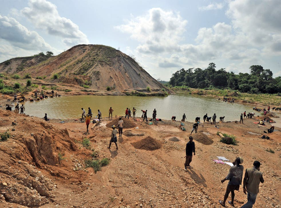 Diamond prospectors filter earth from a river in Koidu, where diamonds were discovered in 1930