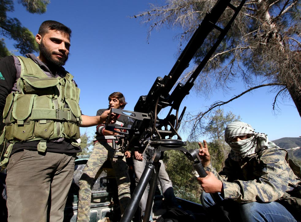 Syrian Turkmen fighters are seen with an anti-aircraft artillery weapon near the northern Syrian village of Yamadi on 24 November 2015