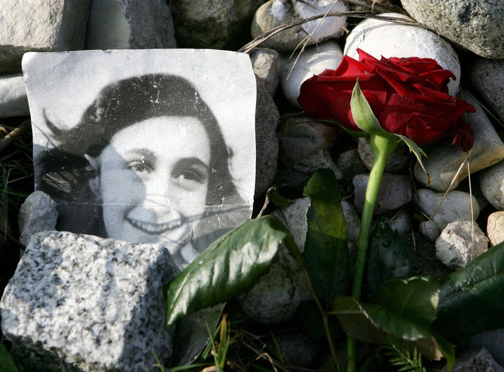 A picture of Anne Frank lies in front of her memorial stone