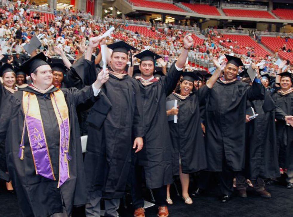 Students show their excitement  during the graduation ceremony for the University of Phoenix at the Arizona Cardinals stadium