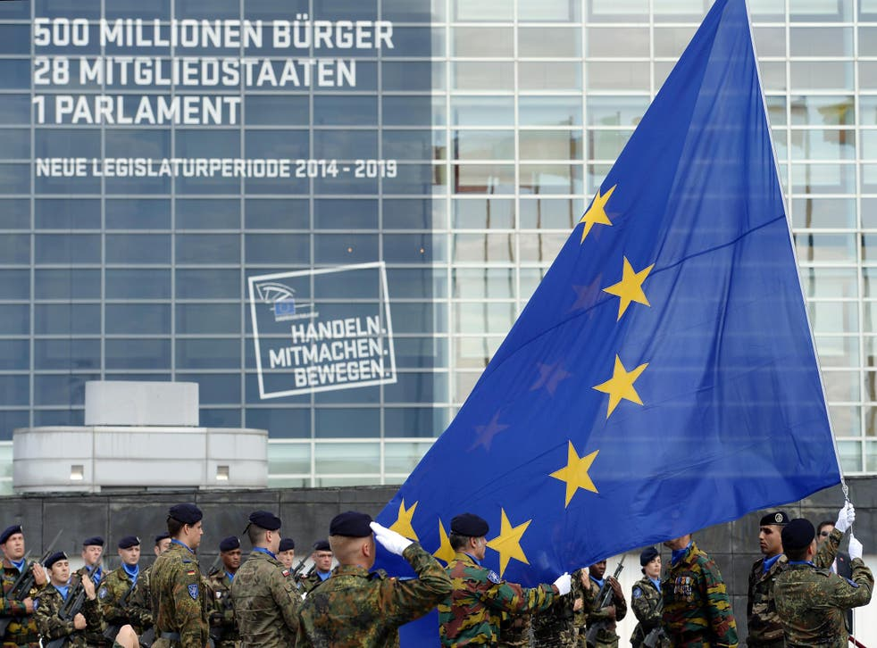 Soldiers of a Eurocorps detachment raise the European Union flag to mark the inaugural European Parliament session on June 30, 2014