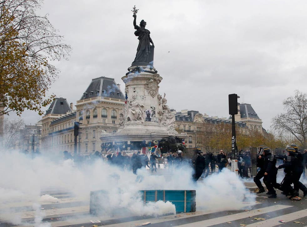Clouds of tear gas fill the air as demonstrators clash with French CRS riot police at the Place de la Republique after the cancellation of the planned climate march