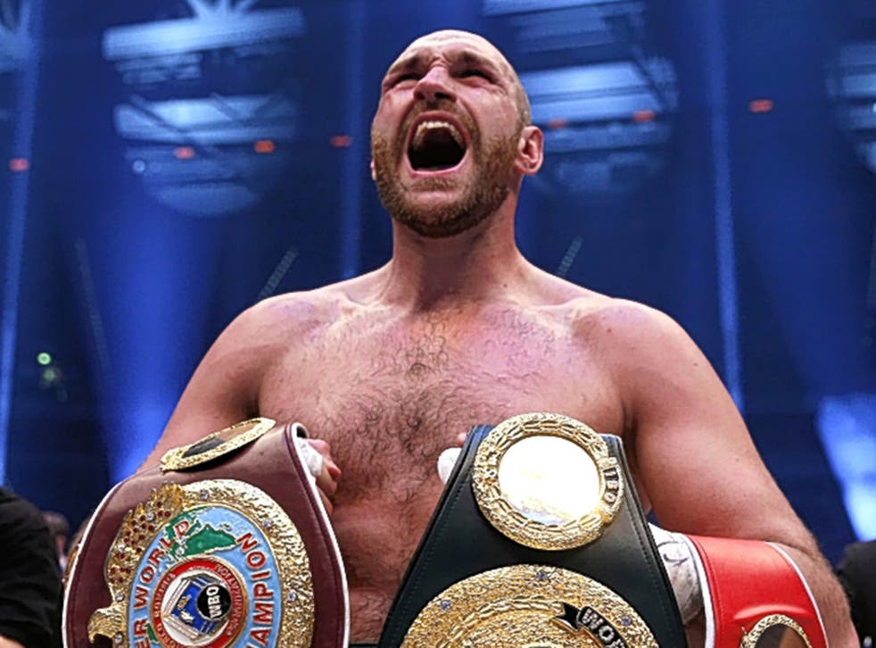 Tyson Fury holds his new belts