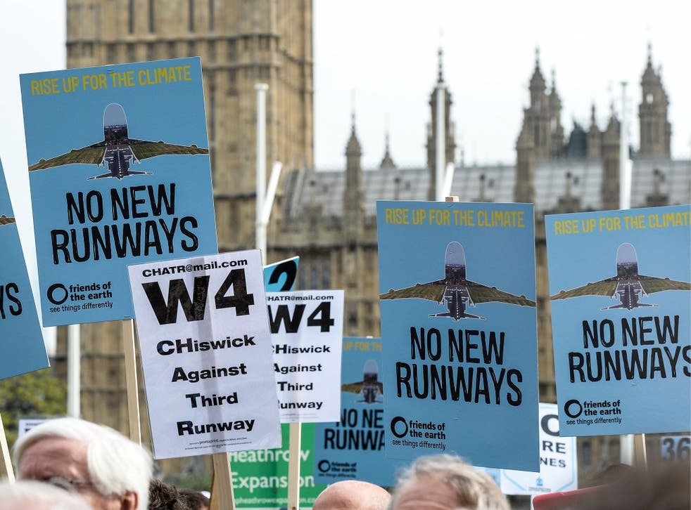 Protesters hold signs during a rally against a third runway at Heathrow airport, in Parliament Square