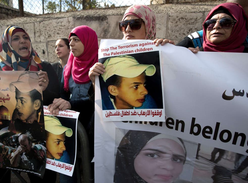 Protesters hold posters of Palestinian teenager Mohammed Abu Khdeir, who was killed last year, outside the district court in Jerusalem on November 30, 2015