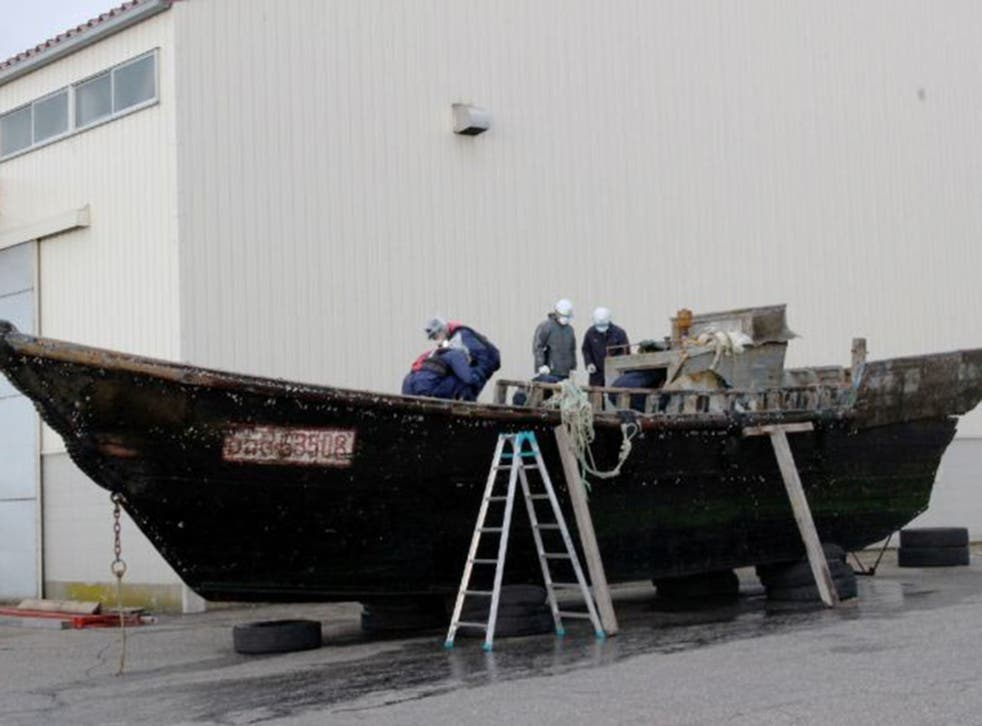 Coast guard officials investigating a wooden boat at the Fukui port, western Japan after the ship was found drifting off the coast of Fukui