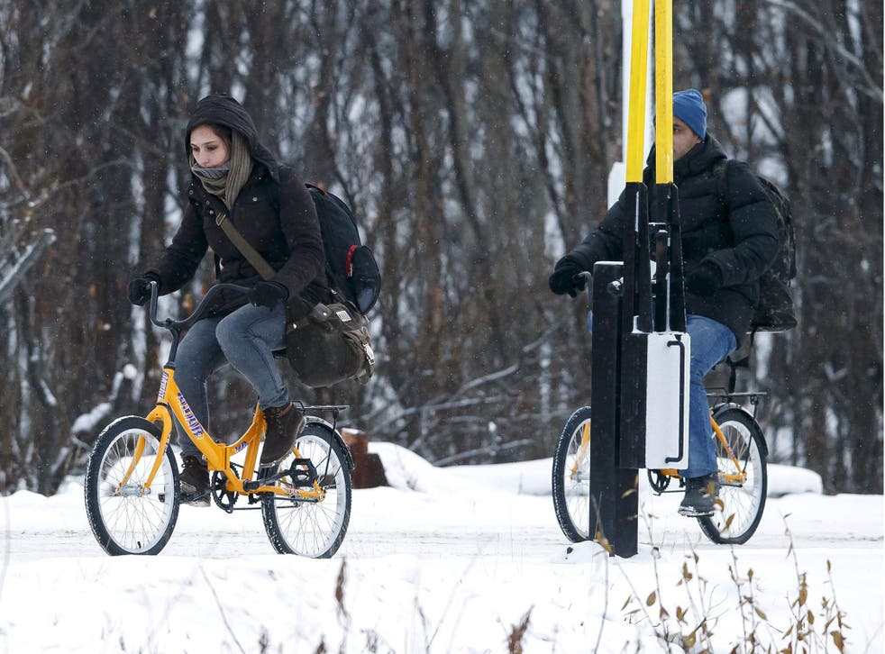 Two refugees on bikes cross the boarder between Norway and Russia