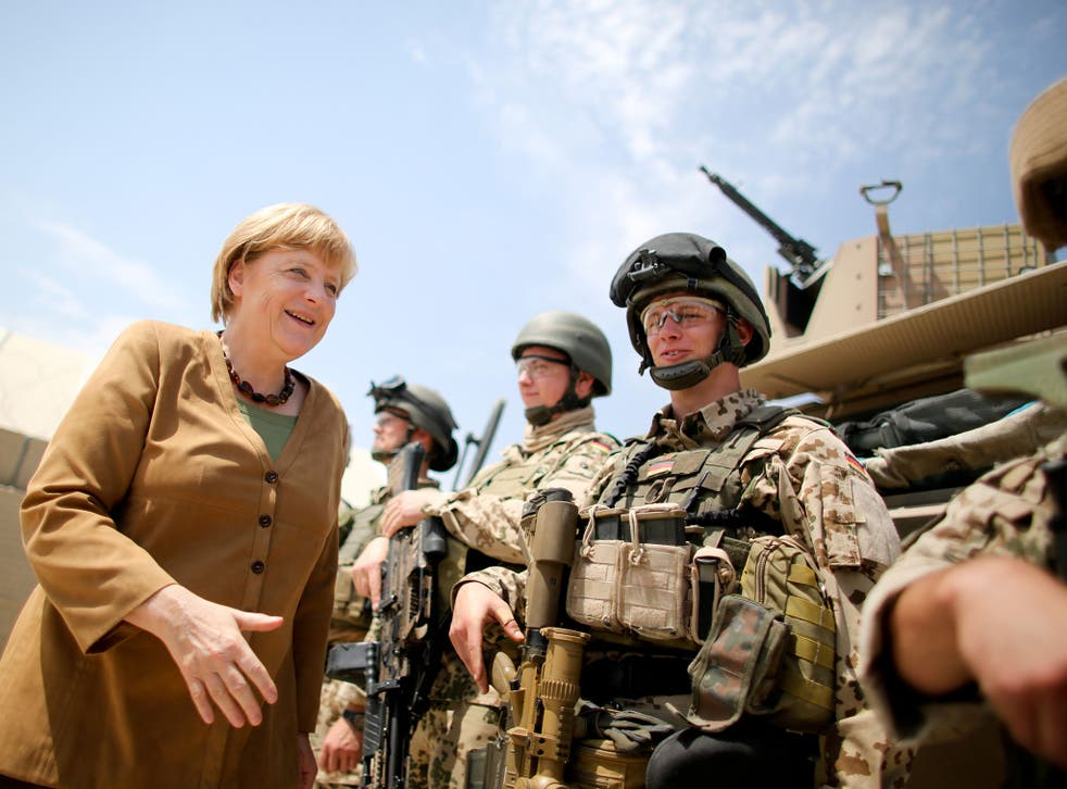 German Chancellor Angela Merkel shakes hands with soldiers of the German armed forces Bundeswehr during her visit on May 10, 2013 at the Bundeswehr base in Kunduz, Afghanistan.