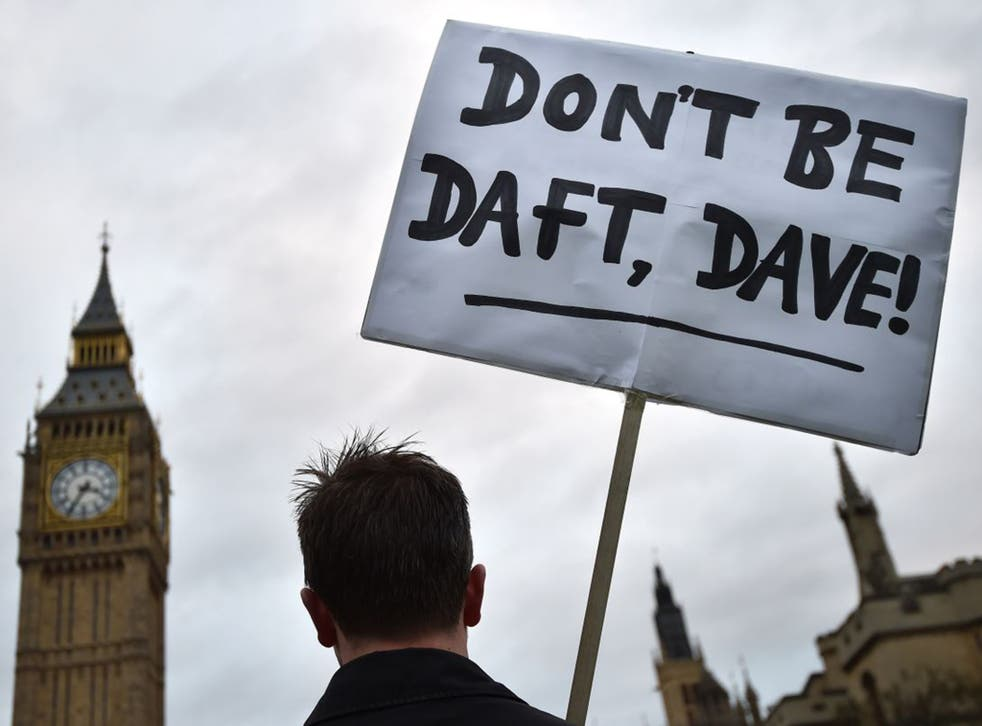 A lone protester opposed to British military action in Syria holds a placard outside the Houses of Parliament
