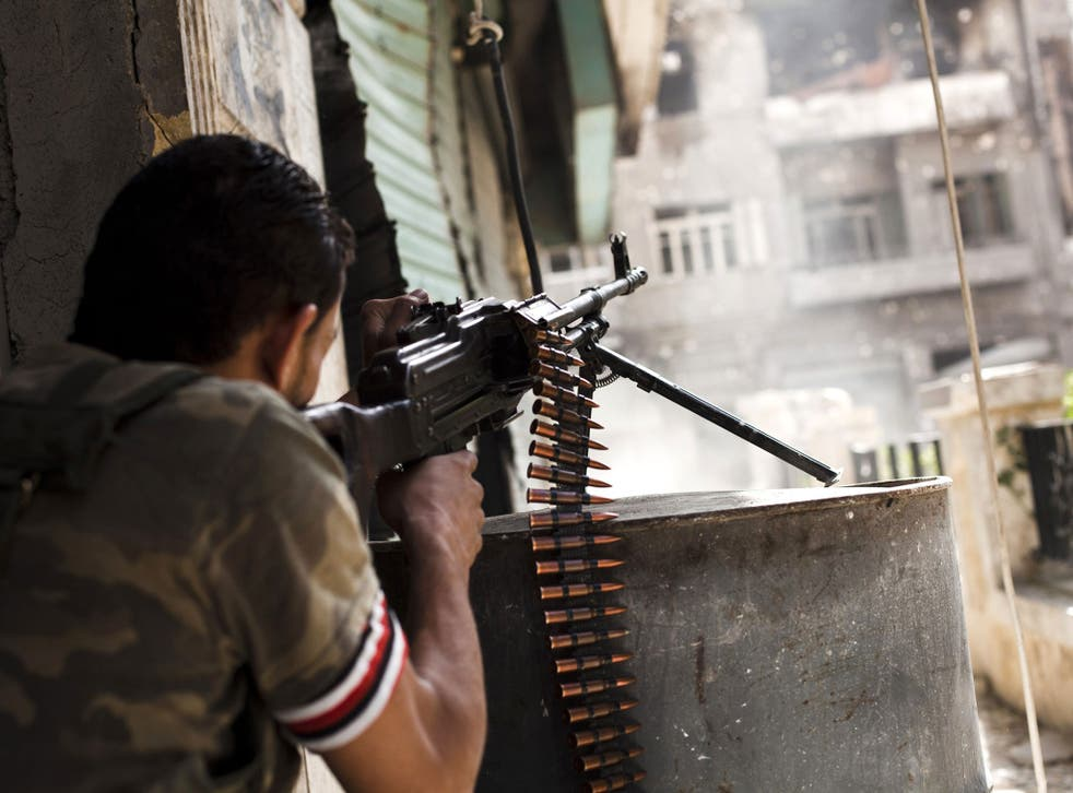 File: A rebel fighter fires his gun against a Syrian government troop position in the Bustan al-Basha area of the northern Syrian city of Aleppo