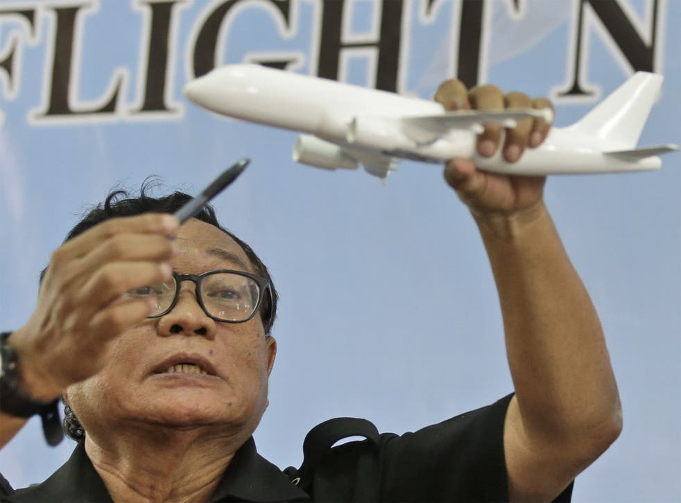 Indonesian National Transportation Safety Committee Chief Investigator Marjono Siswosuwarno holds up a model plane as he explains the movement of AirAsia Flight QZ8501, at a news conference in Jakarta on Tuesday