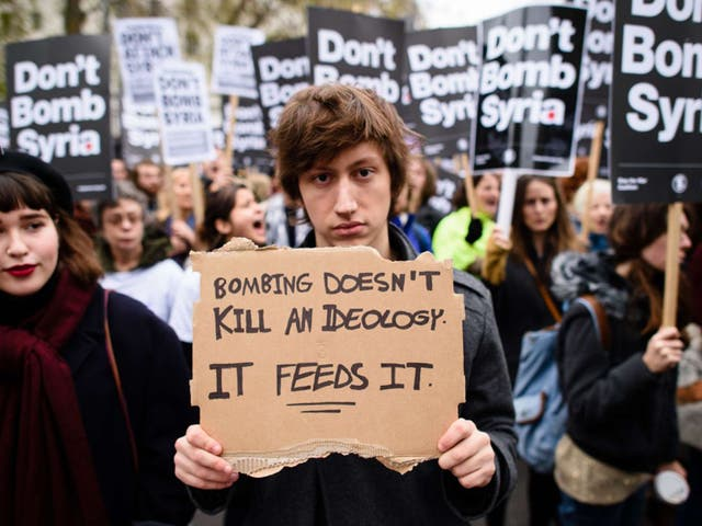 Demonstrators hold placards as they protest against the British government's proposed involvement in air strikes against the Isis