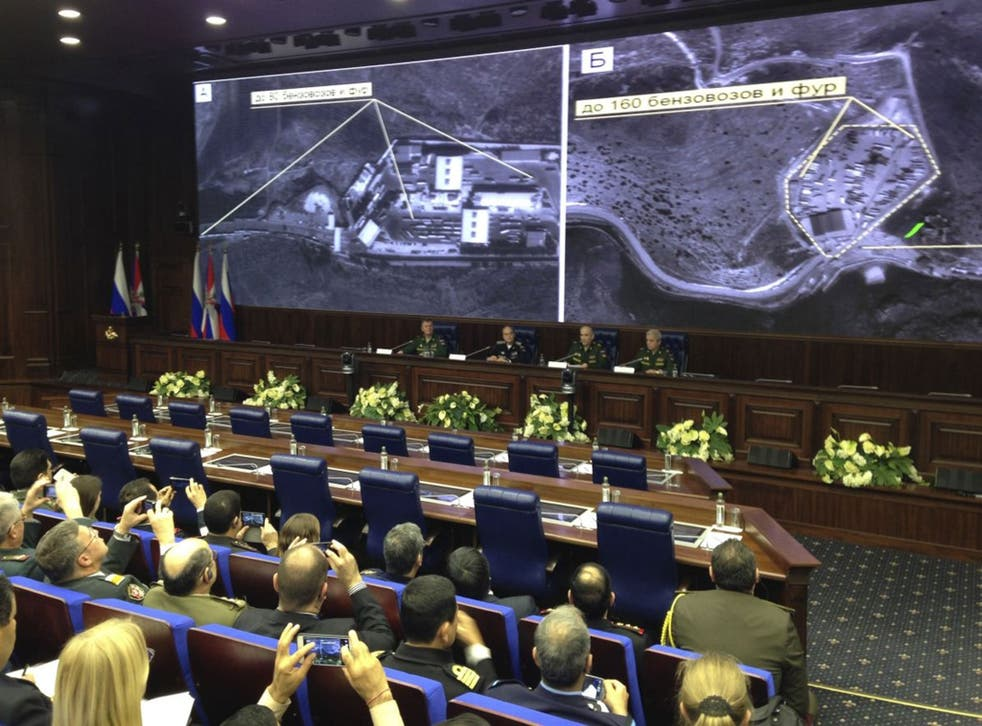 Russian top military officials speak to the media in front of an aerial images they say are oil trucks near Turkey's border with Syria