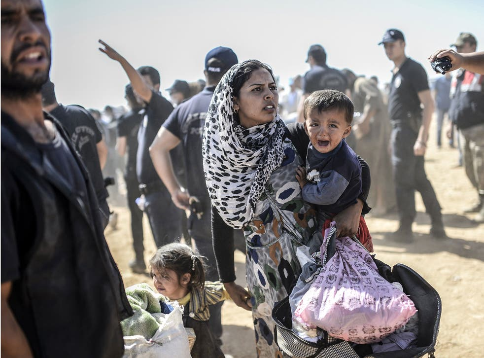 A Syrian Kurdish woman crosses the border between Syria and Turkey at the southeastern town of Suruc in Sanliurfa province on 23 September, 2014