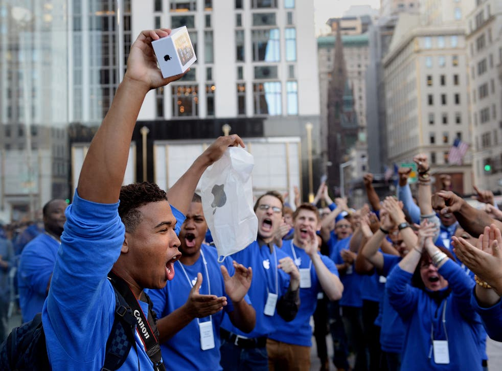 Brian Ceballo emerges from the Apple Store on Fifth Avenue as the first to purchase the new iPhone 5 to the cheers of Apple store employees September 20, 2013 in New York