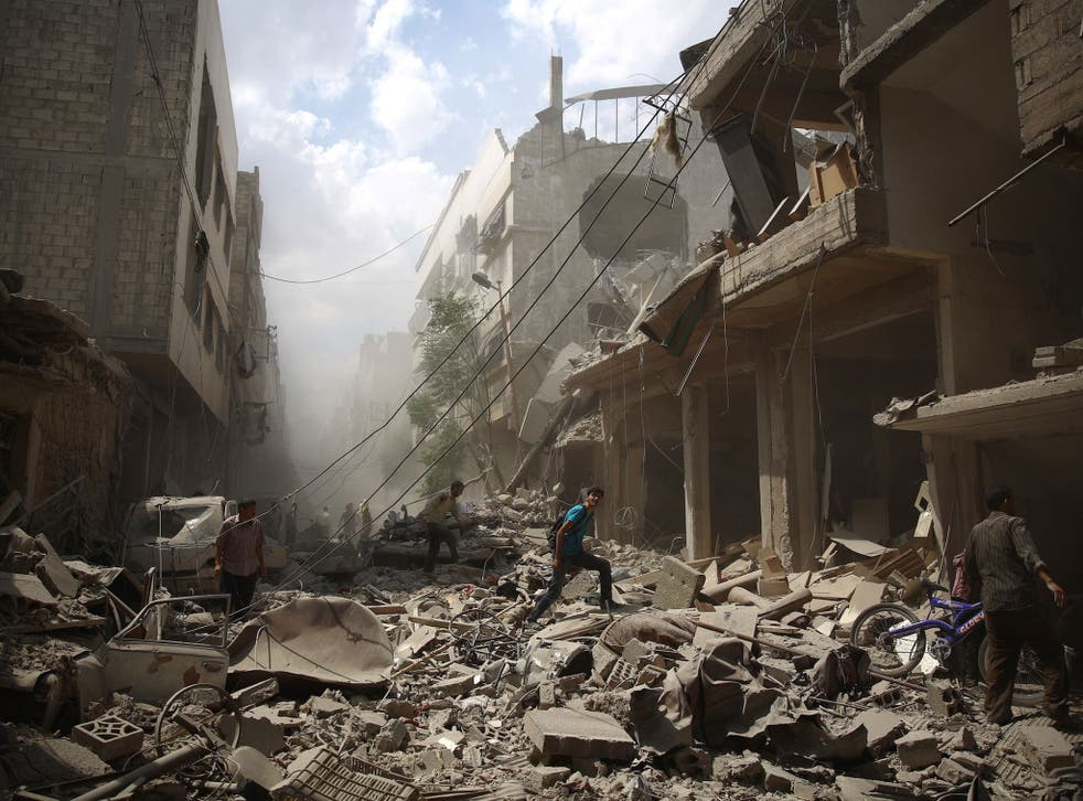 Syrians walk amid the rubble of destroyed buildings following reported air strikes by regime forces in the rebel-held area of Douma, east of the capital Damascus