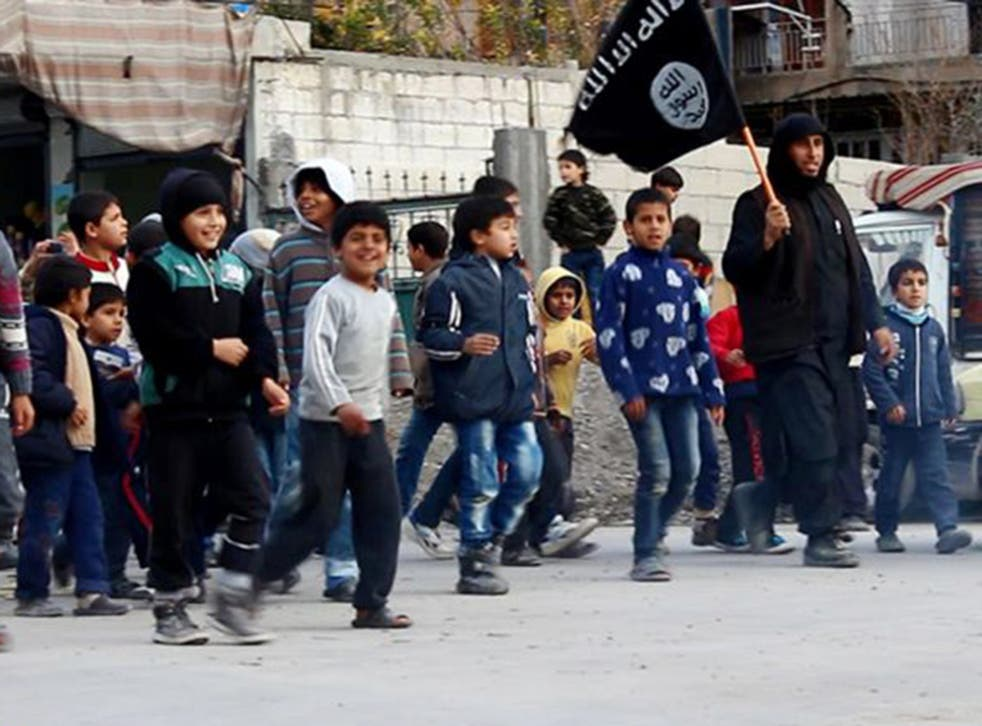 Syrian boys follow an Isis militant in Raqqa