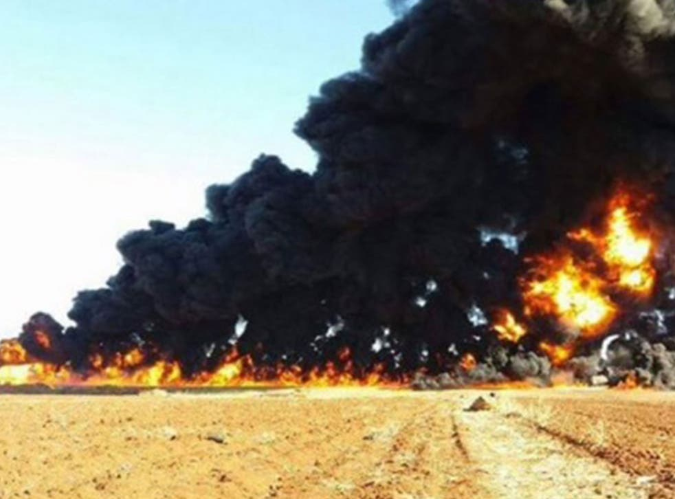 Thick black smoke billowing into the sky from the remains of the oil tanker after it was hit by a Russian air strike