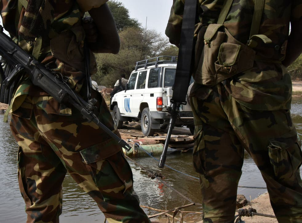 A picture taken on January 27, 2015 shows Chadian soldiers watching as a UN vehicle from a United Nations' refugee agency (UNHCR) convoy crosses a branch of lake Chad