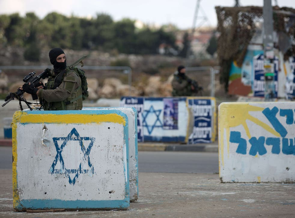An Israeli soldier stands guard at a deserted junction between Jerusalem and Hebron