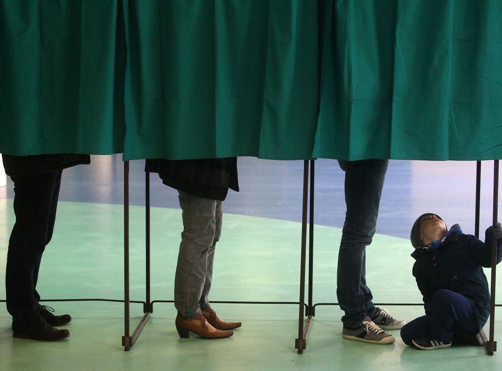 Voters stand in a polling booth during first round of regional elections, in Henin-Beaumont