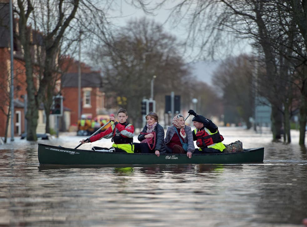 A rescue team helps to evacuate people from their homes after Storm Desmond floods Carlisle