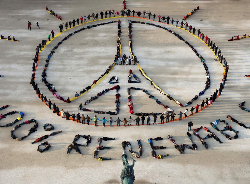 """People make the """"Pray for Paris"""" sign along with the slogan """"100 percent renewable"""" in Paris, on the sidelines of the COP21 climate change conference"""