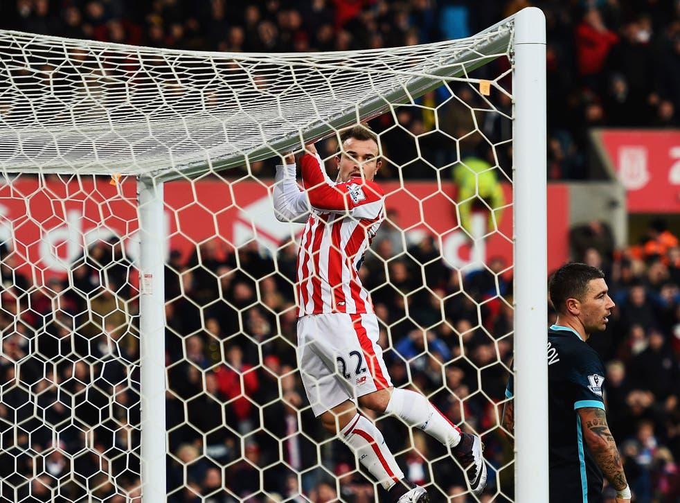 Stoke winger Xherdan Shqiri holds onto the crossbar during the win over Manchester City