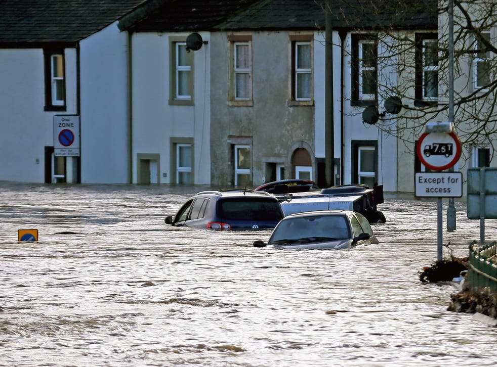 Water rises above cars as flooding blights the market town of Cockermouth