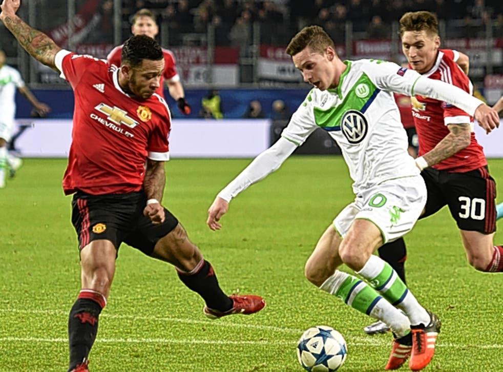 Wolfsburg midfielder Julian Draxler takes on Manchester United winger Memphis Depay