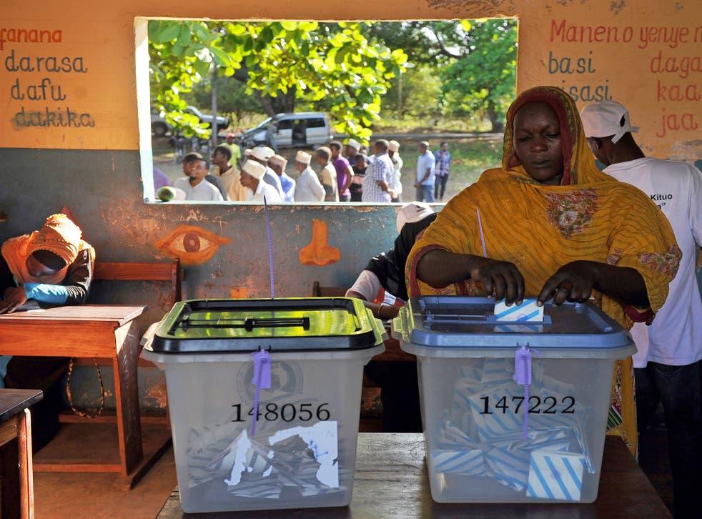 A Tanzanian woman casts her ballot for the Tanzanian presidential elections in Zanzibar
