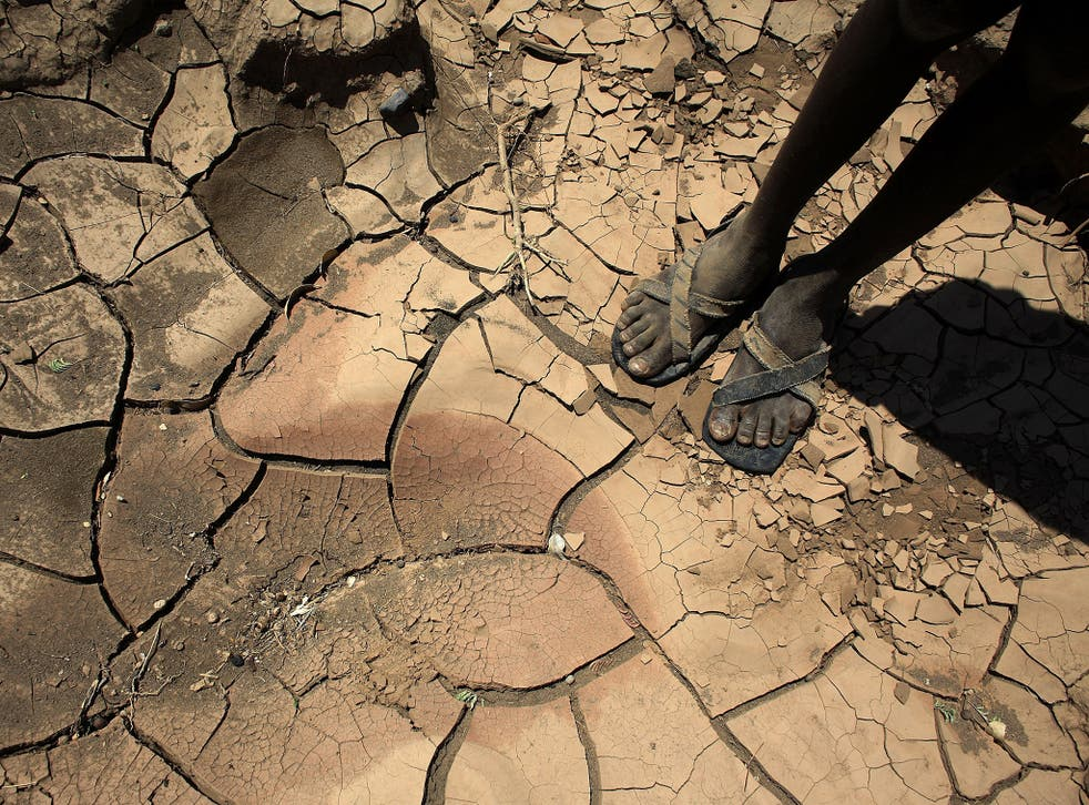 A young boy from a remote tribe in northern Kenya stands on a dried up river bed