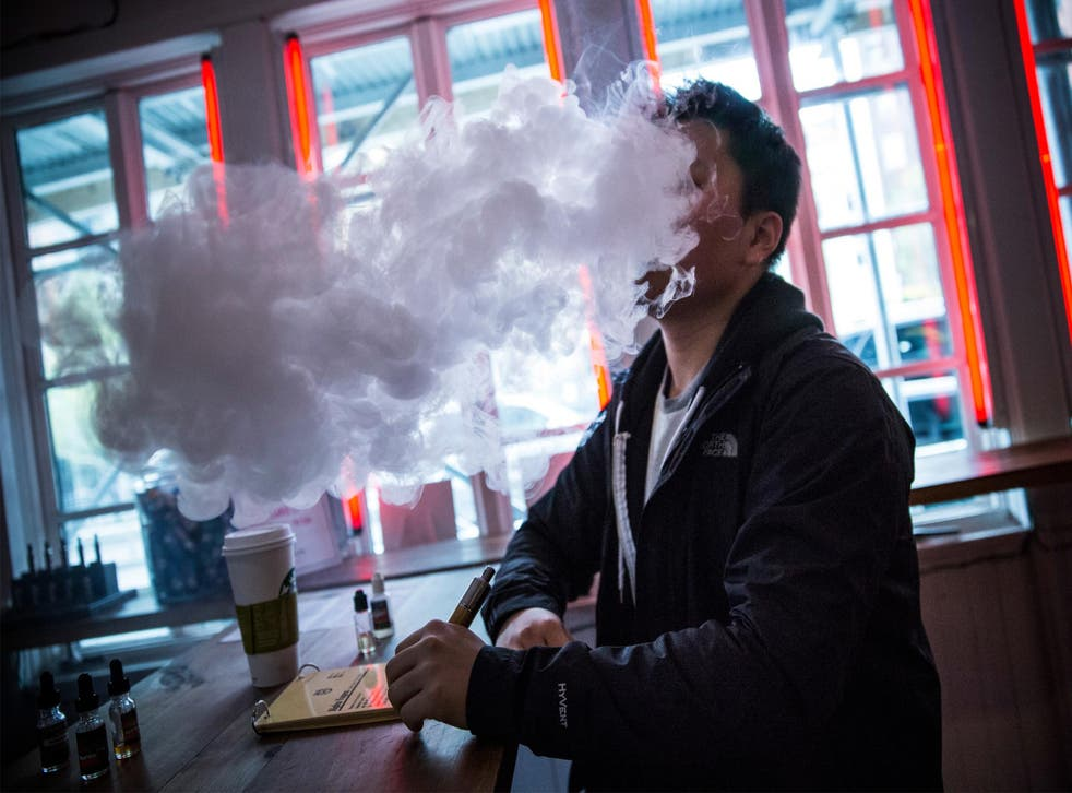 A man vapes in a New York e-cigarette shop