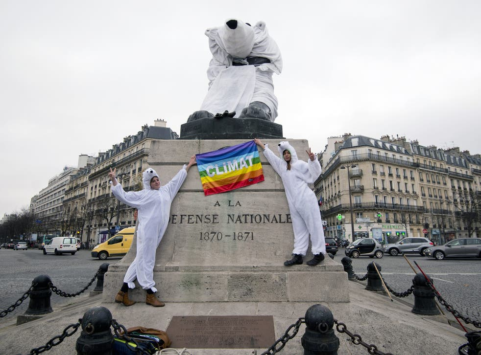 """Two women dressed as polar bear hold a peace flag with an inscription reading """"Climat"""" as the gestures a victory sign in front of the """"Lion of Belfort"""" statue, also dressed as a polar bear, on the Denfert-Rochereau place in Paris."""