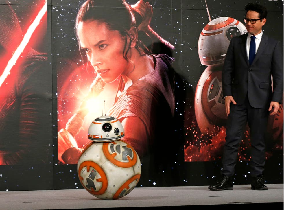 """Director J.J. Abrams watches BB-8 droid moving during a press conference""""Star Wars: The Force Awakens"""" at a hotel in Urayasu, near Tokyo"""