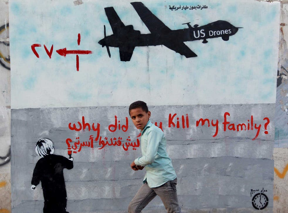 A Yemeni boy runs past a mural painted on the wall of the capital in Sanaa