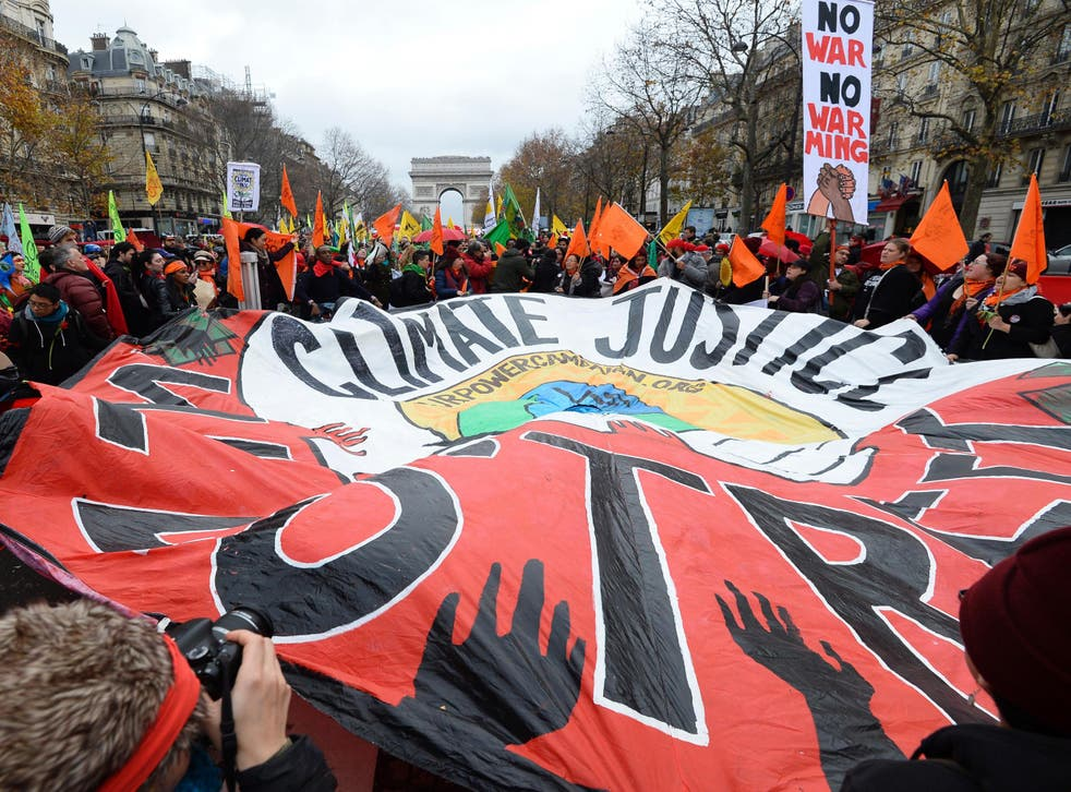 Protesters outside the talks in Paris. French foreign minister Laurent Fabius said the draft deal acknowledged the concept of 'climate justice' - a key demand from campaigners and a coalition of at risk countries