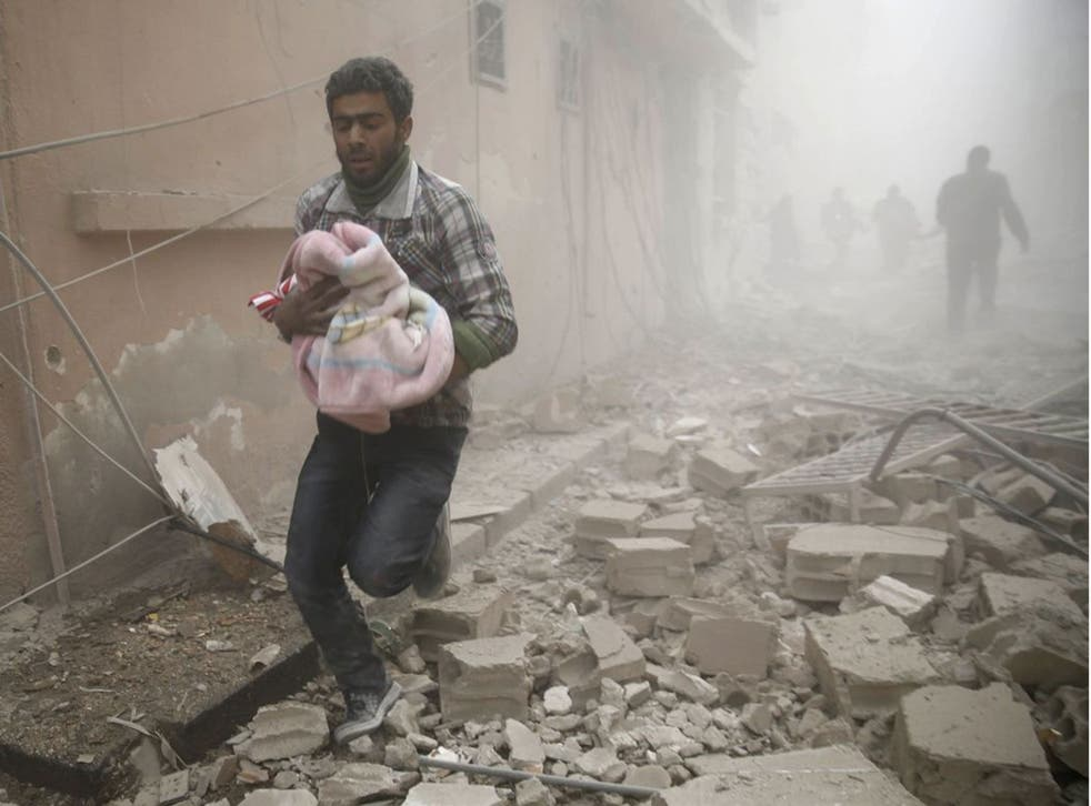 A Syrian man carries a baby wrapped in a blanket following air strikes on the town of Douma in the eastern Ghouta region, a rebel stronghold east of the capital Damascus, on 13 December, 2015